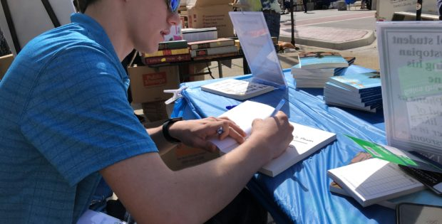 Aaron autographs copies of his new book The King's Pawn at the 2019 Printers Row Literature Fest. Photo courtesy Ray Hanania